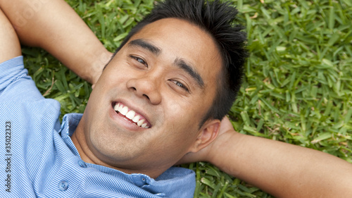 Smiling man laying in grass