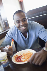 Black man eating french fries at diner
