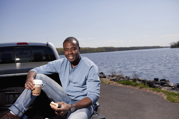 Black man sitting in truck bed eating lunch
