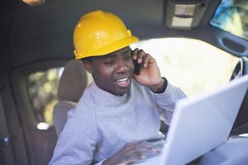 Black man wearing hard hat in vehicle using laptop