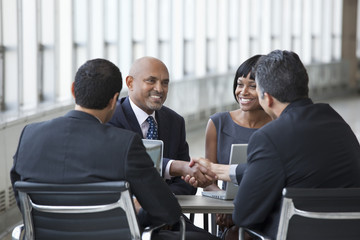 Smiling business people shaking hands in meeting