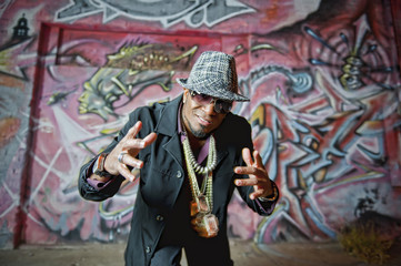 Hip African American man gesturing near graffiti