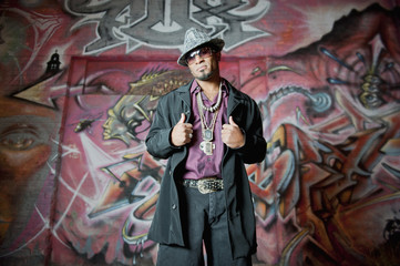 Hip African American man standing near graffiti
