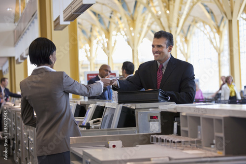 Clerk giving smiling businessman airplane ticket at airport counter