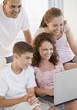 Smiling Hispanic family using laptop together