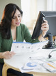 Hispanic woman reading computer assembly instructions