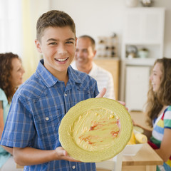 Smiling boy displaying empty plate with family at table in background