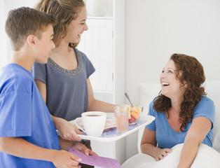 Hispanic children bring mother breakfast in bed
