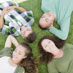 Hispanic family laying in grass together