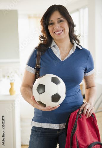 Hispanic woman holding backpack and soccer ball