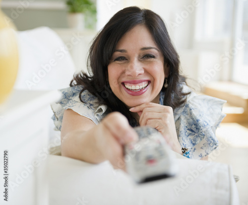 Smiling Hispanic woman changing channel with remote control