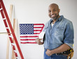 African American construction worker holding hard-hat near American flag