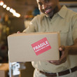 "African American deliveryman holding out box with ""fragile"" sticker"