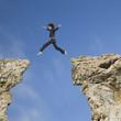Mixed race businesswoman jumping over gap between cliffs