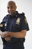 Smiling African American policeman holding cap