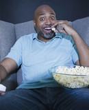 African American man eating popcorn and watching television