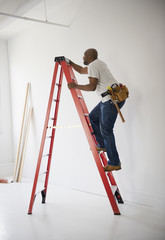 African American construction worker climbing ladder