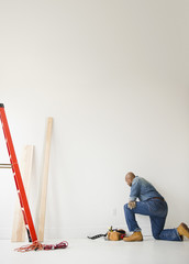 African American construction worker kneeling to look at wall