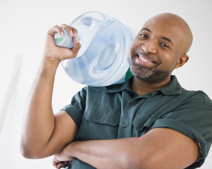 African American deliveryman holding water bottle