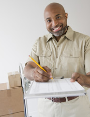 African American deliveryman holding out clipboard for signature
