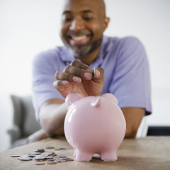 Smiling African American man putting coins in piggy bank