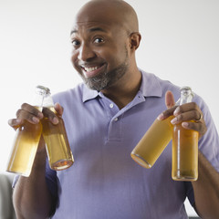 Smiling African American man holding beer bottles