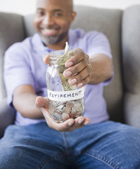 Smiling African American man holding out jar with retirement money