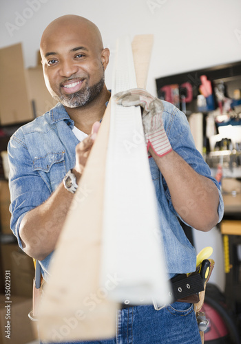 African American construction worker carrying lumber