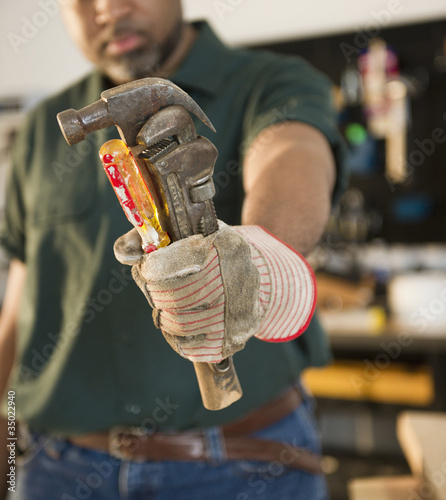 """African American carpenter holding screwdriver, wrench and hammer"""