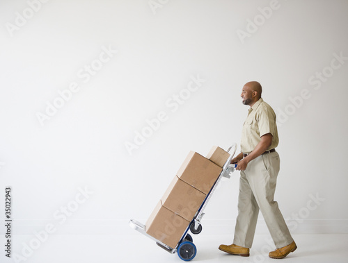 African American deliveryman pushing hand truck with boxes