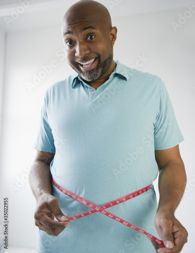 Happy African American man measuring his waistline