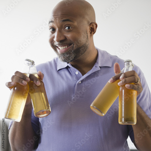 Smiling African American man holding beer bottles
