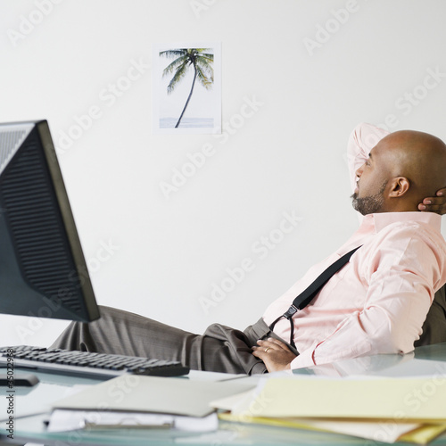 African American businessman looking at picture of palm tree