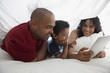 Black family using digital tablet underneath sheet