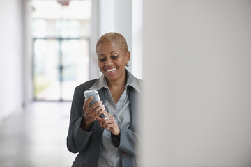 Smiling Black businesswoman text messaging on cell phone