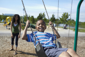 Black mother pushing son on swings