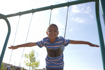 Black boy playing on swing set