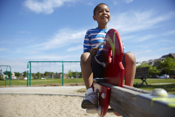 Black boy playing on seesaw at playground
