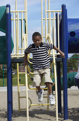 Black boy jumping down from playground equipment