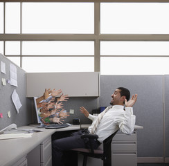 Hands reaching out from computer trying to grab Hispanic businessman