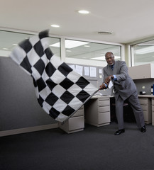 African American businessman waving checkered flag in office