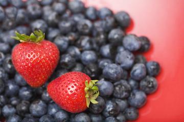 Strawberries on pile of blueberries