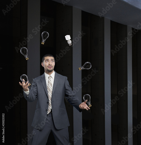 Hispanic businessman juggling old-fashioned light bulbs and one CFL light bulb
