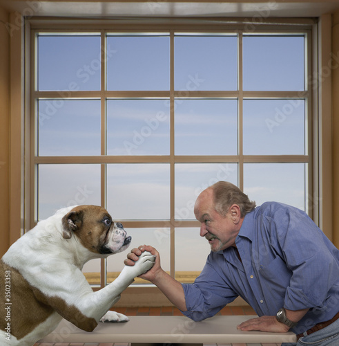 Caucasian man arm wrestling with dog