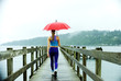 Caucasian woman in sportswear with red umbrella on pier