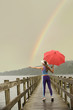 Caucasian woman in sportswear with red umbrella on pier catching rainbow