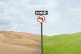 Road signs pointing at green grass and desert