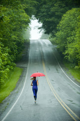 Caucasian woman running on remote road with umbrella