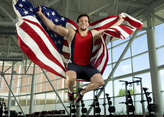 Caucasian athlete jumping with American flag