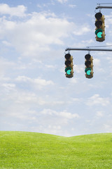 Green traffic lights over grass field